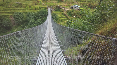 Trekking across a suspension bridge at Chomrong