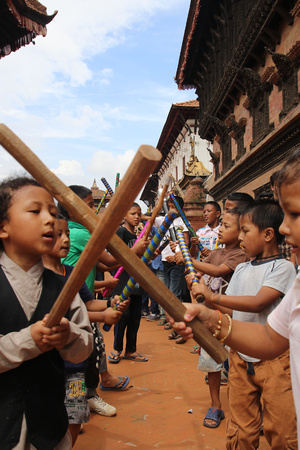 Children hit sticks in tune to drums in Bhaktapur Durbar Square during Gai Jatra