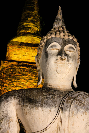 Buddha statue and chedi lit up at night in Sukhothai