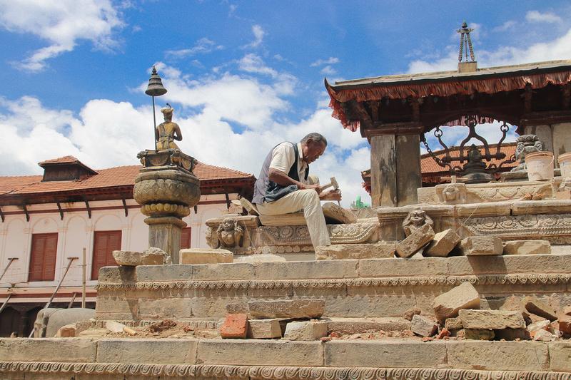 A stone mason traditionally rebuilding Vatsala Durga temple in Bhaktapur