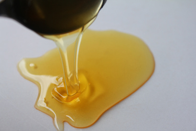 Pouring a spoon of honey onto a plate
