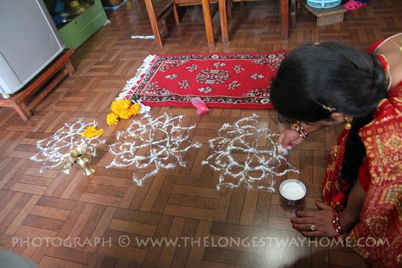 A sister makes rangoli on the floor