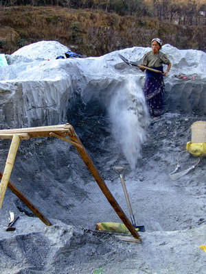Old woman shoveling sand through a makeshift sieve in a river mine