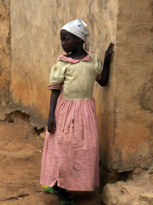 Village African girl standing by a corner