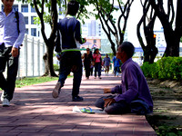 People walking by a man asking for money on the streets of Kota Kinabalu