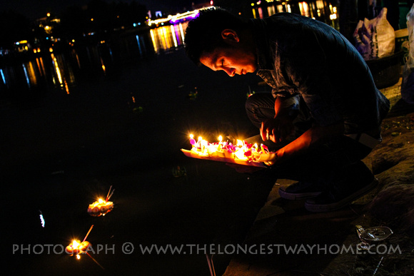 Man lighting candle boat at Loi Krathong