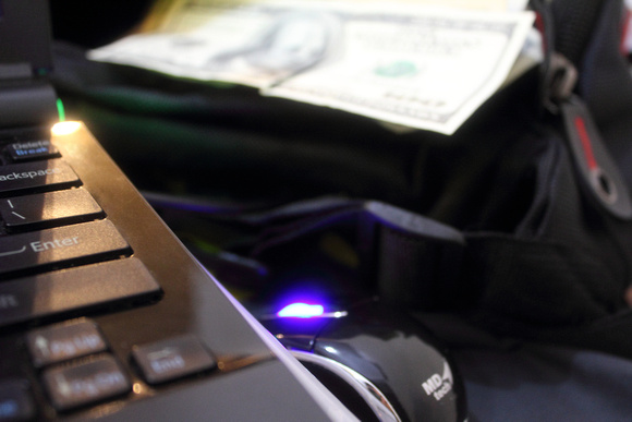 Laptop with mouse and money in the background