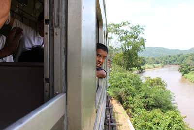 Young Thai enjoying a weekend train trip over some a shaky bridge