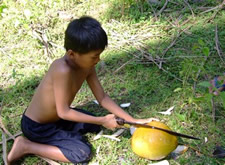 Filippino boy tries to cut open a coconut